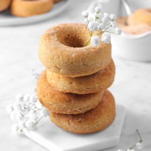 four cinnamon donuts stacked on a marble coaster with flowers, cinnamon sugar, and more donuts behind
