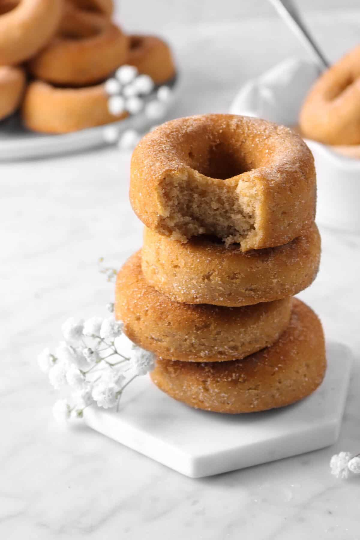 stacked four cinnamon donuts with a bite out of one, flowers, and more donuts behind