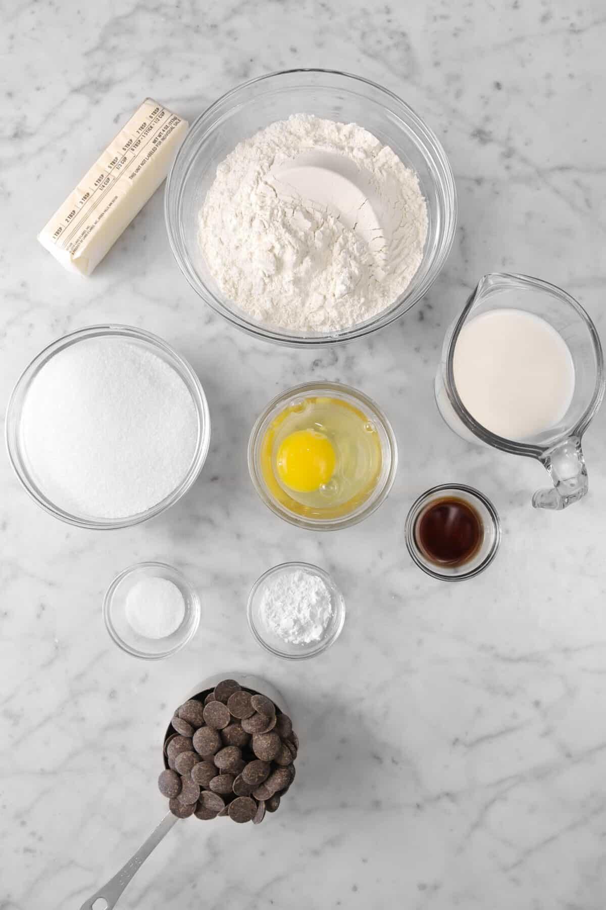flour, butter, sugar, egg, milk, vanilla, baking powder, salt, and chocolate chips on a marble counter