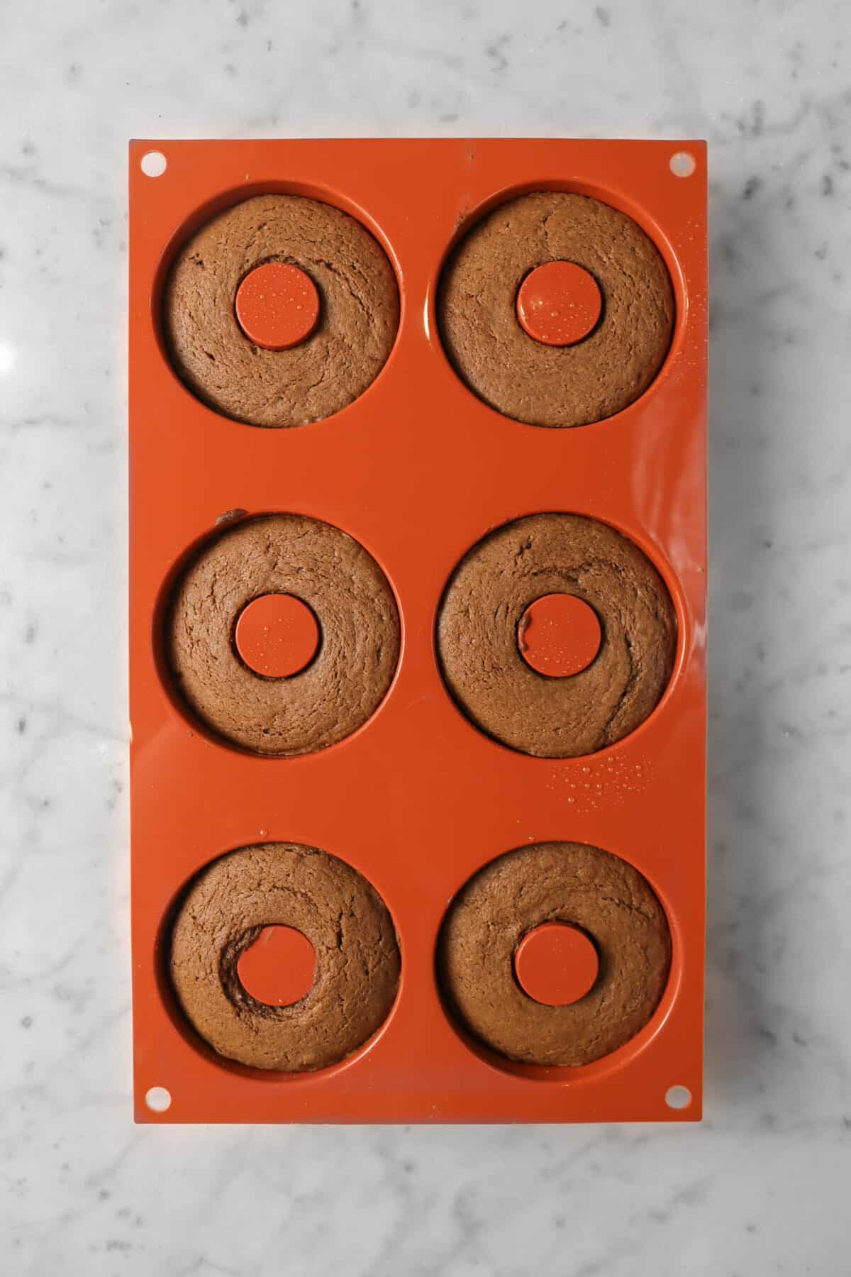 chocolate donuts in a donut mold on a marble counter