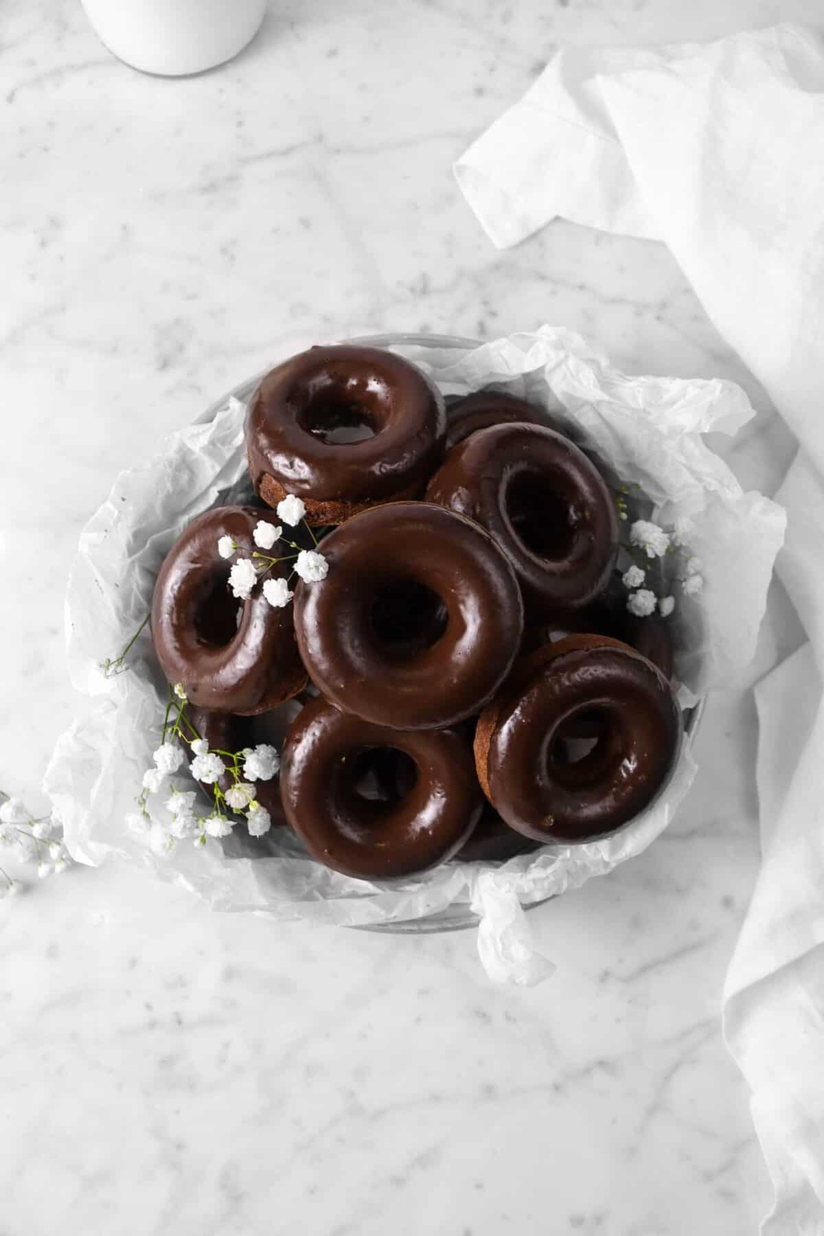overhead shot of chocolate donuts with parchment paper, flowers, and a white napkin