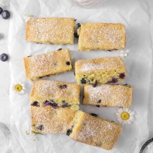 Lemon Blueberry Snack Cake sliced with powdered sugar, fresh flowers, blueberries, and a glass of milk