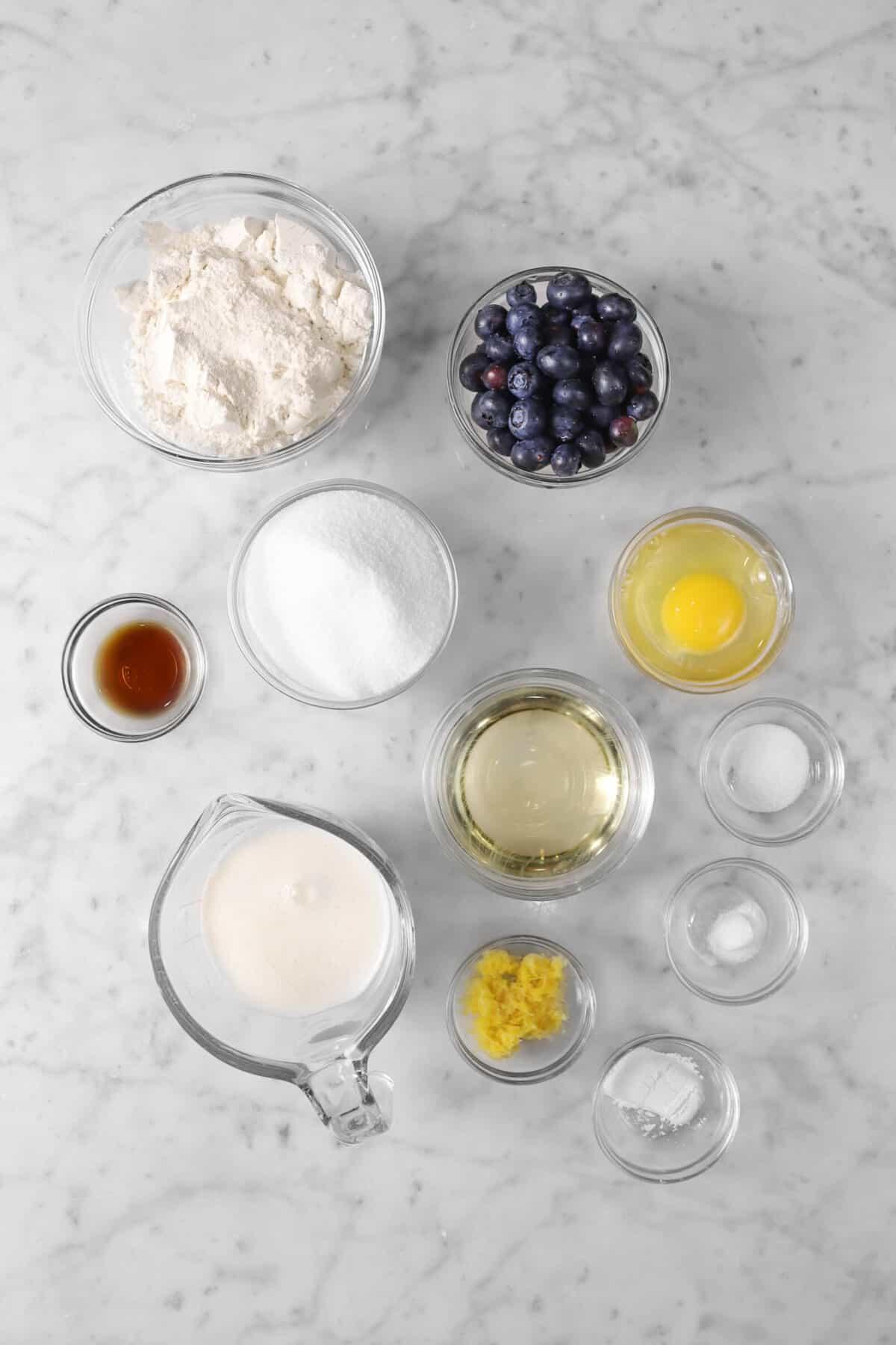 flour, blueberries, sugar, vanilla, egg, oil, buttermilk, lemon zest, baking powder, baking soda, and salt on a marble counter