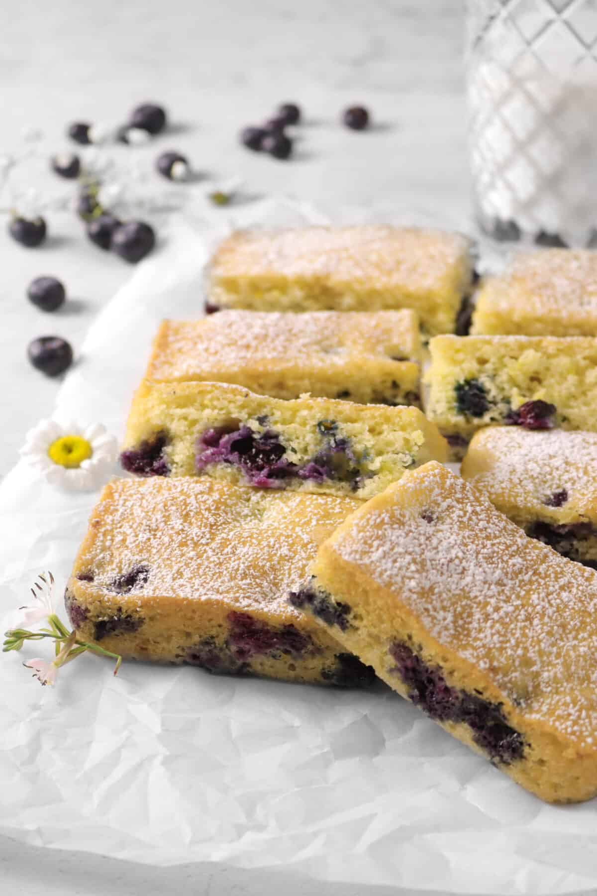 Lemon Blueberry Snack Cake sliced on parchment paper. blueberries, fresh flowers, and glass of milk