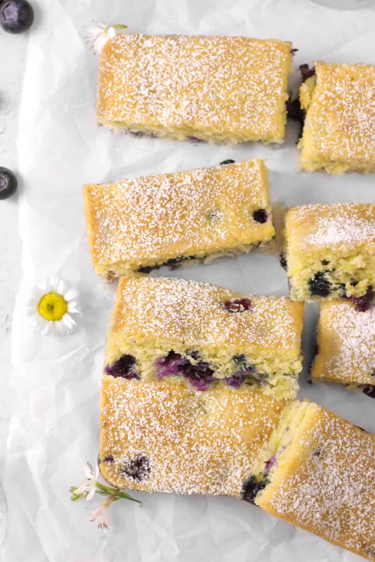 snack cake on parchment paper with powdered sugar, flowers, and blueberries