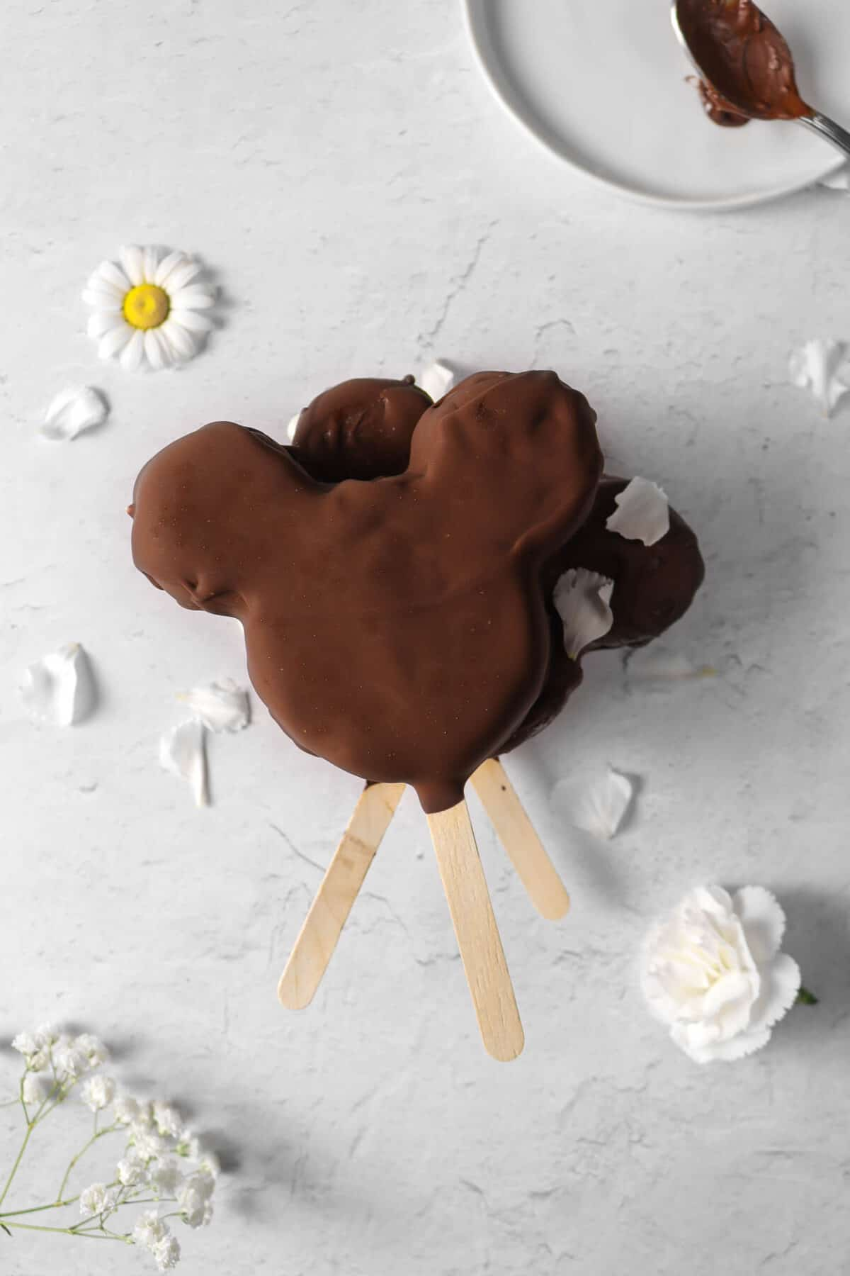 three stacked mickey ice cream bars with flowers and a chocolate covered spoon