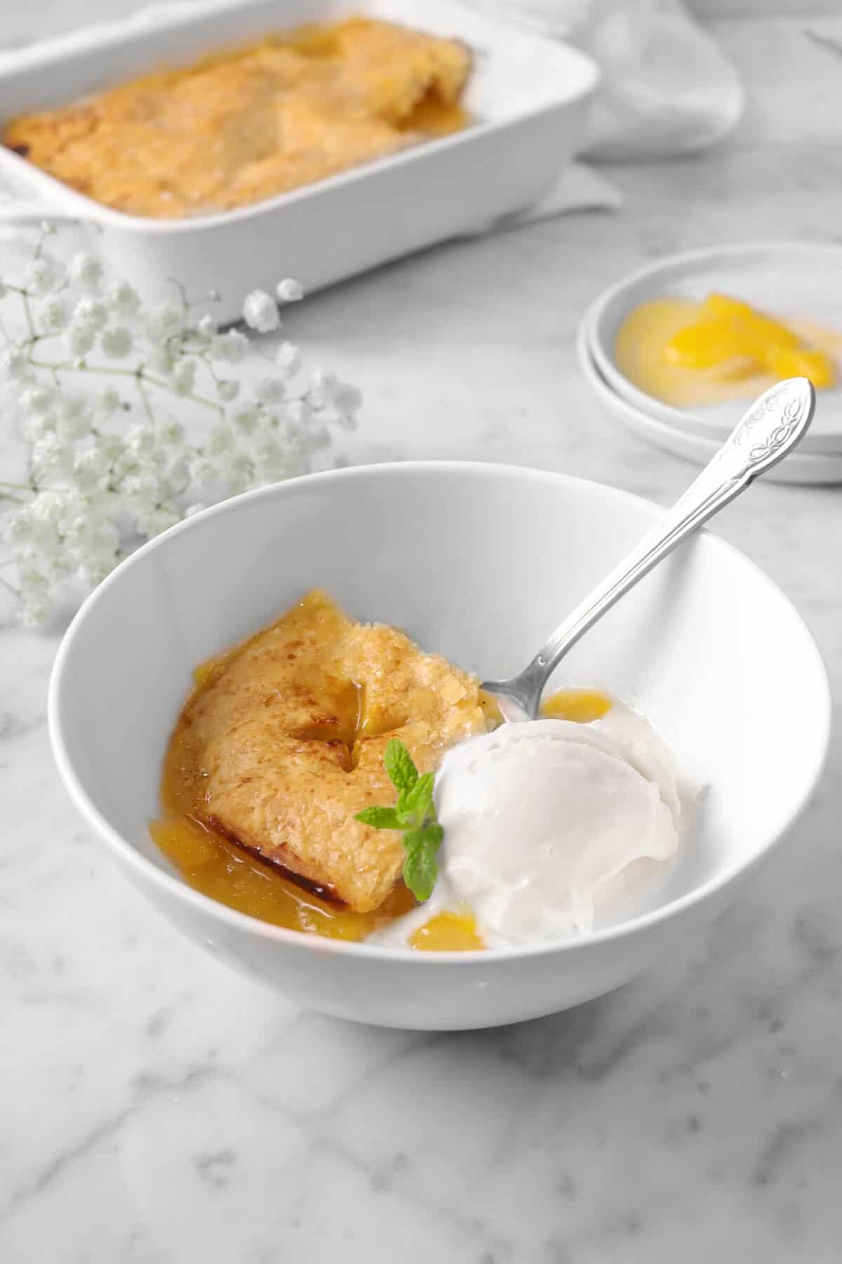 peach cobbler in a bowl with ice cream and a spoon, plates, flowers, and baking pan in background