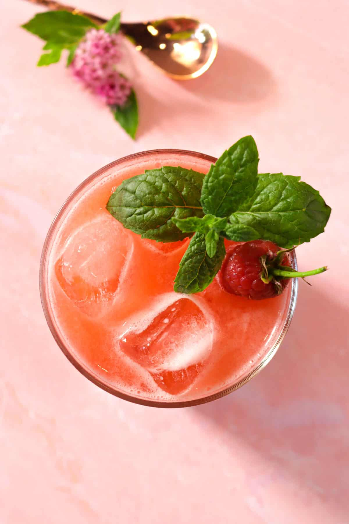 raspberry lemonade on a pink board with a mint sprig, flowers, and a copper spoon
