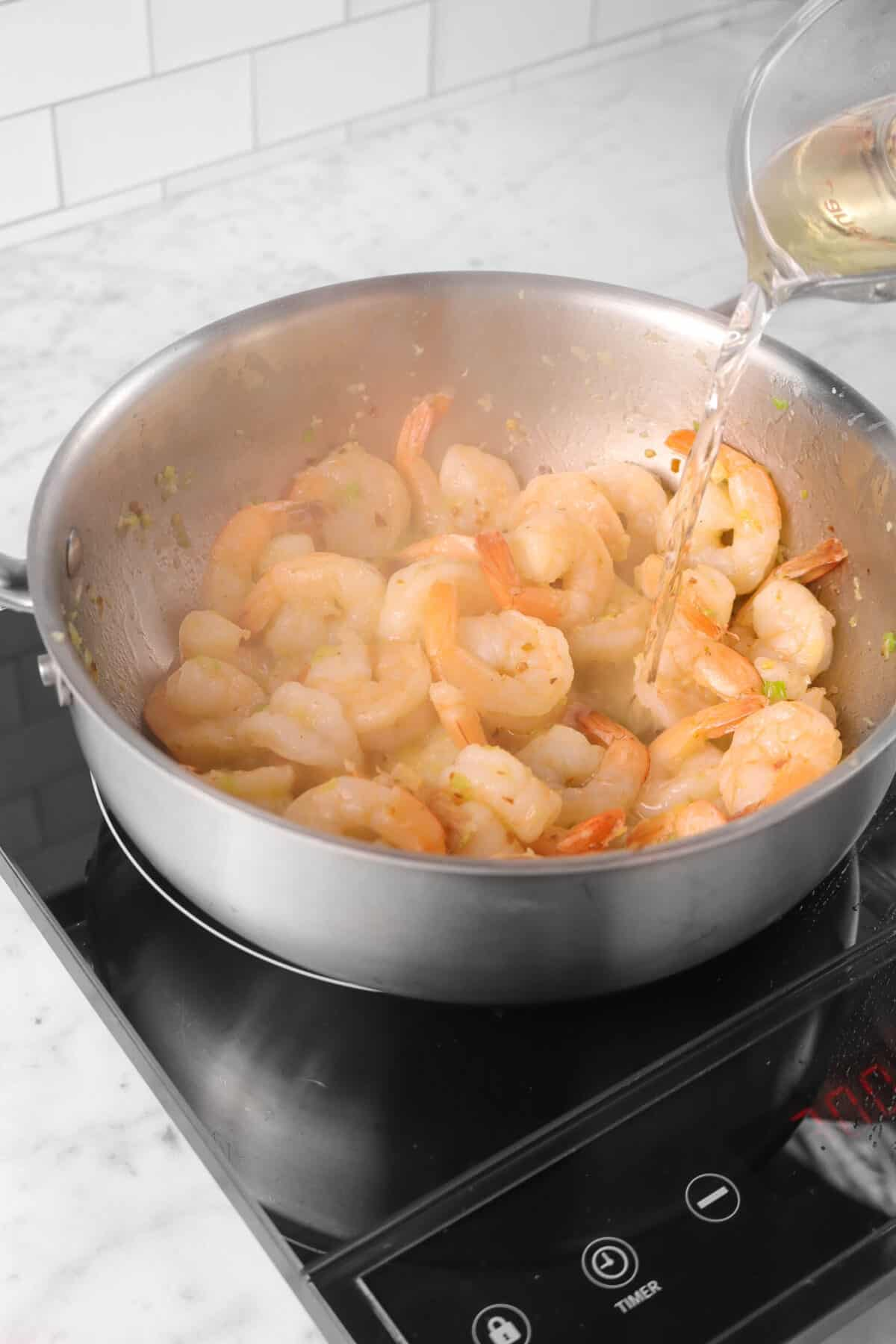 white wine being added to shrimp scampi