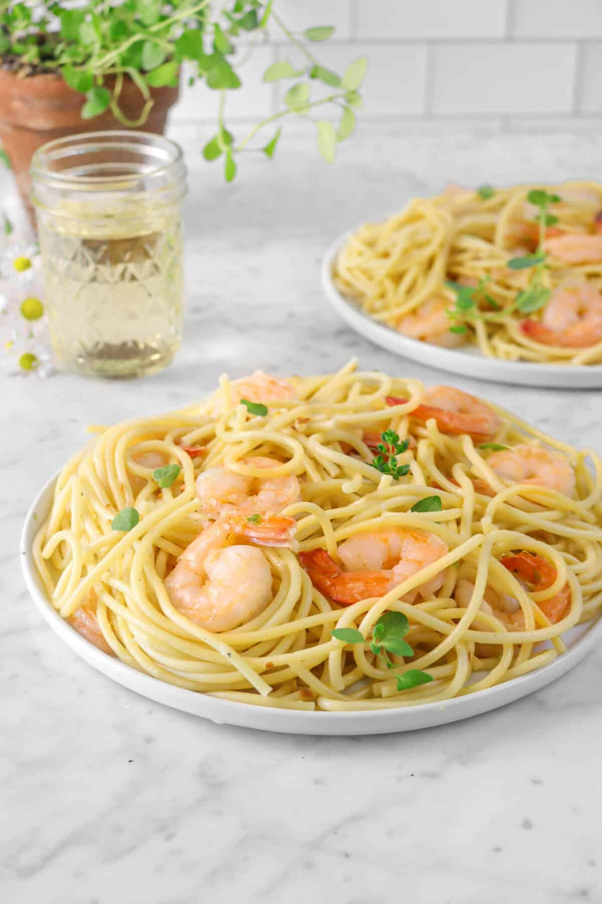 shrimp scampi on two white plates with a jar of white wine, flowers, and oregano