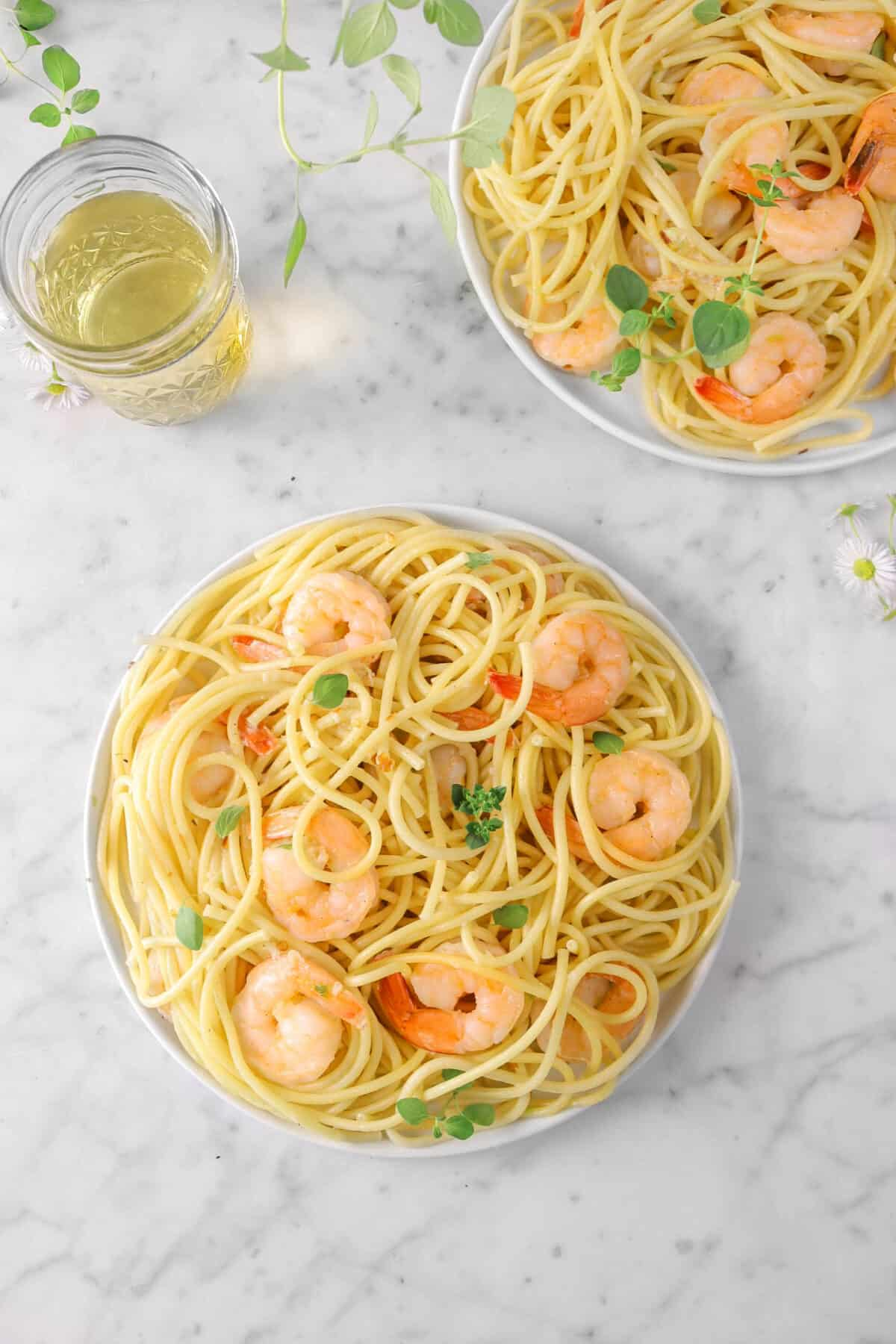 two plates of shrimp scampi with oregano, flowers, and white wine