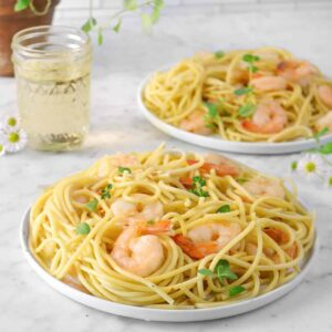 two white plates of shrimp scampi with a pot of oregano, flowers, and white wine