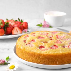 strawberry snack cake on a white plate with flowers, and strawberries