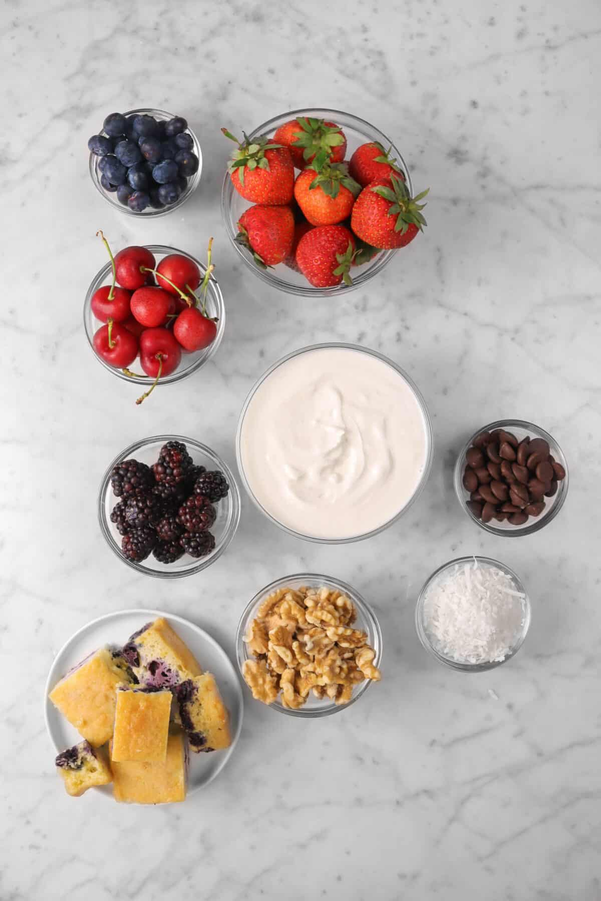 blueberries, strawberries, cherries, baclberries, blueberry cake, walnuts, yogurt, coconut, and chocolate on a marble counter