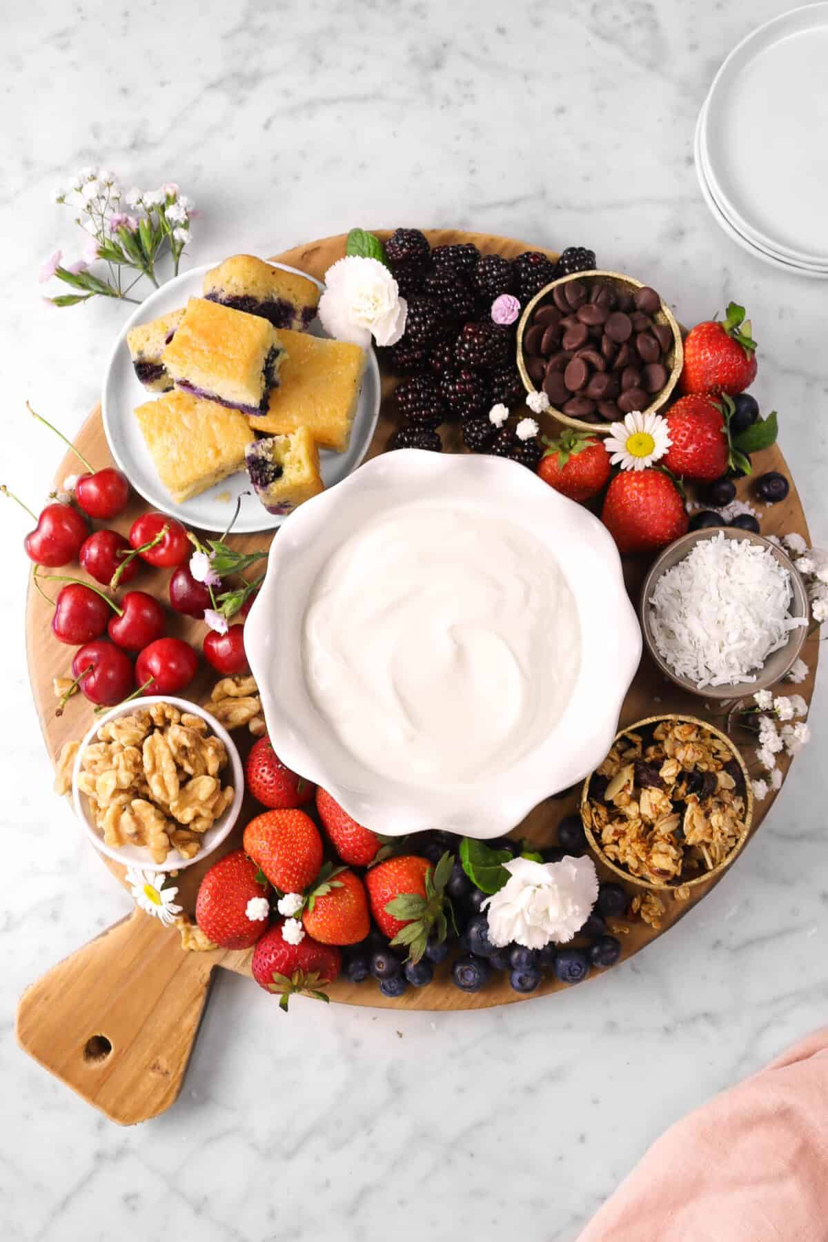 a wood board with fruits, yogurt, cake, flowers, chocolate, granola, and nuts on marble counter with plates and a pink napkin