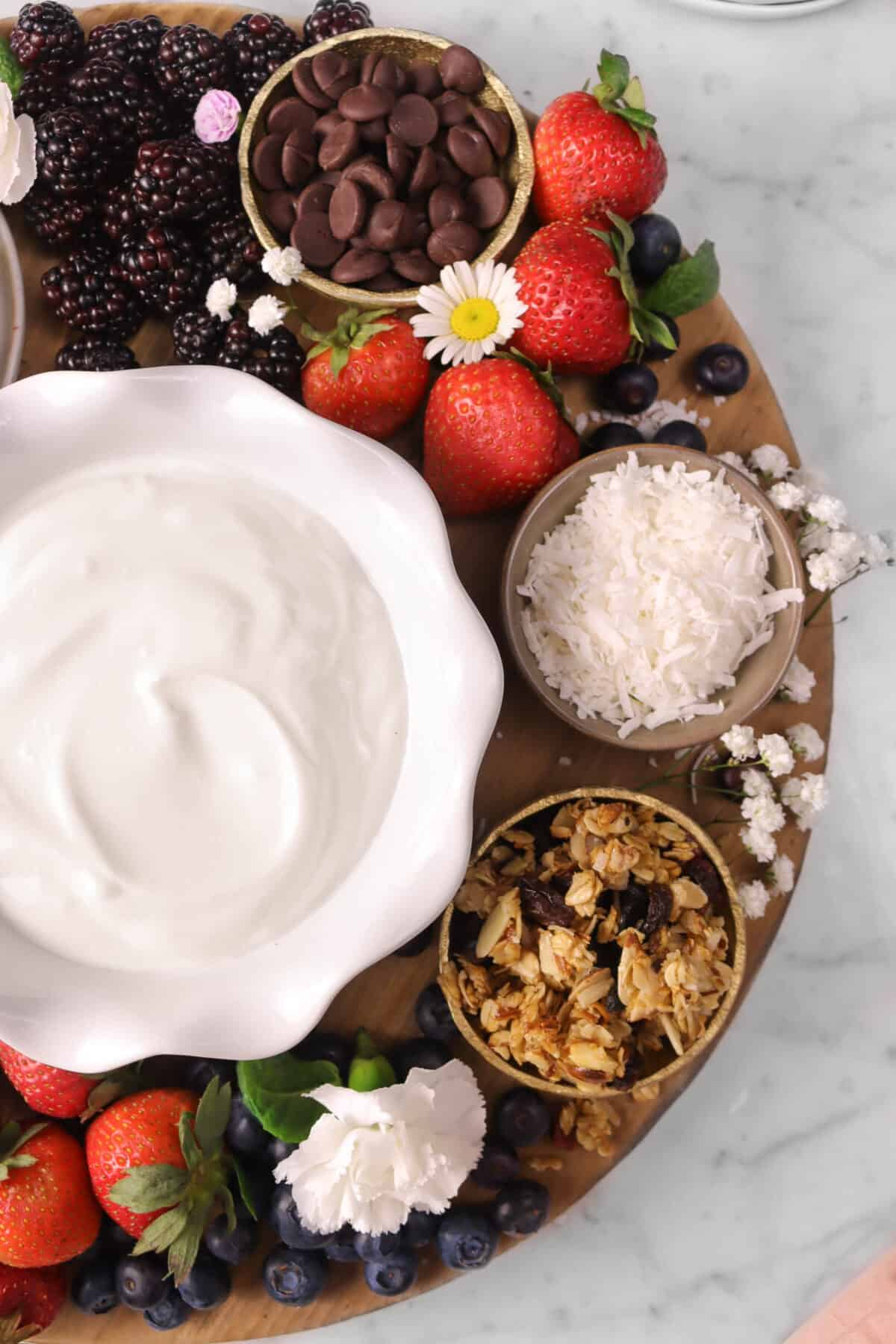 yogurt, berries, granola, coconut, and chocolate on a board