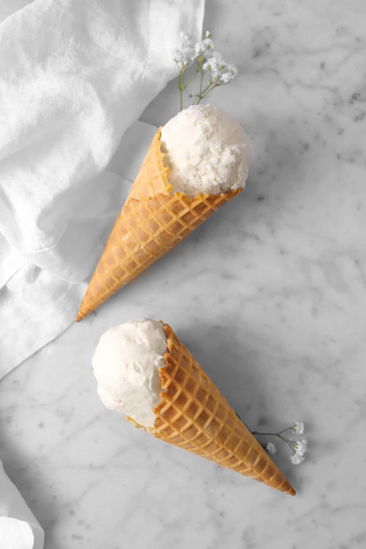two vanilla ice cream cones on marble counter with flowers and napkin