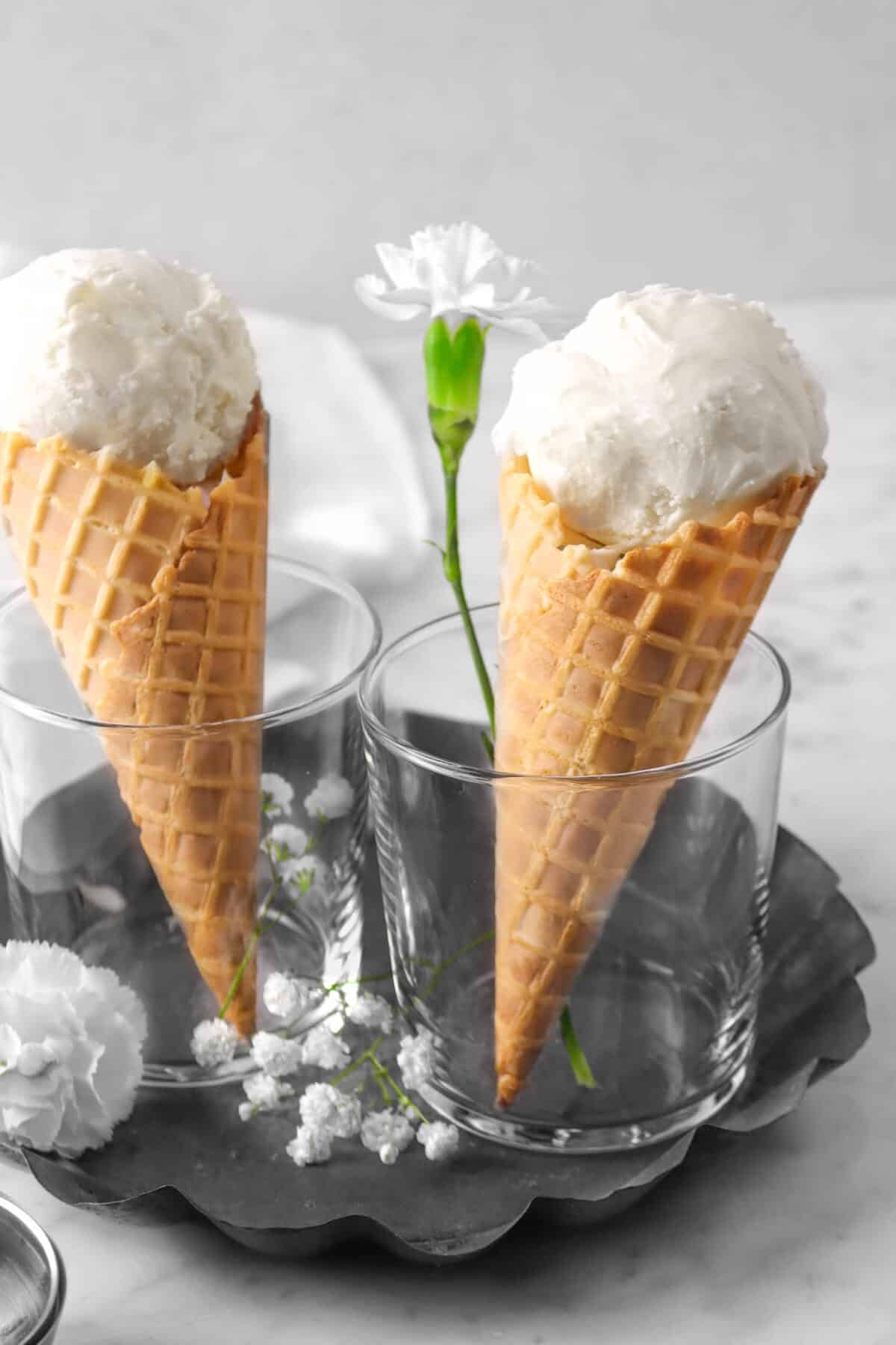 two vanilla ice cream cones with flowers, in glasses, in a pie pan