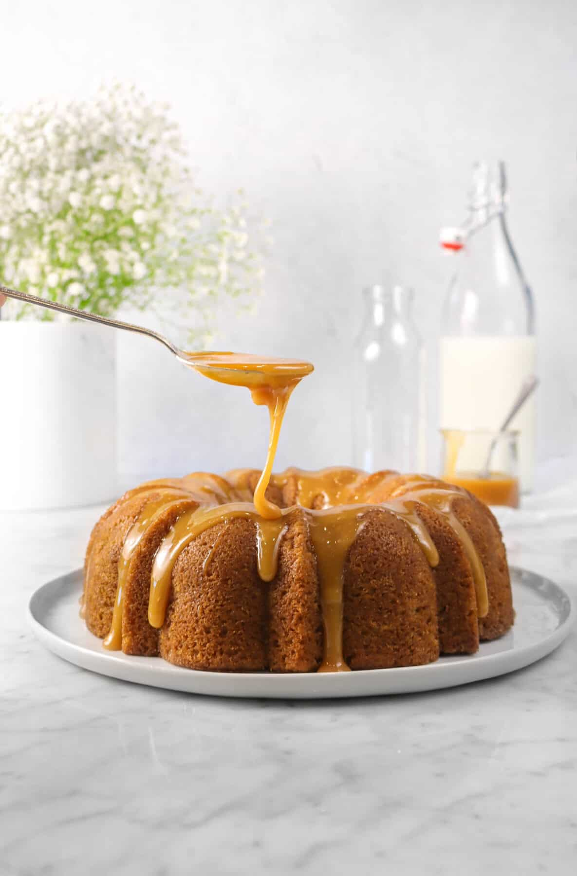 apple cinnamon cake on a white plate with caramel being drizzled onto it