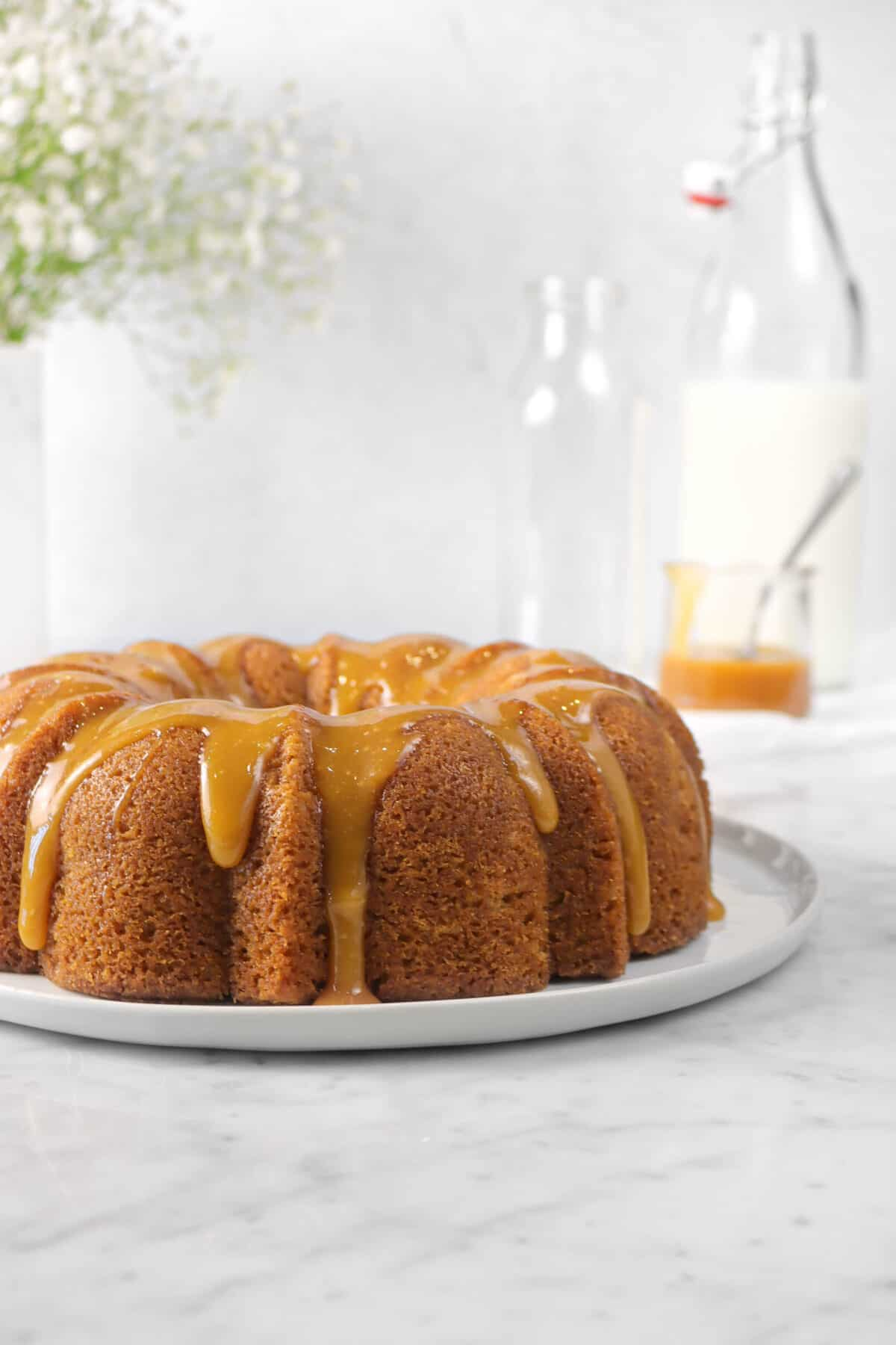 bundt cake on a white plate with caramel sauce, flowers, and milk in the background