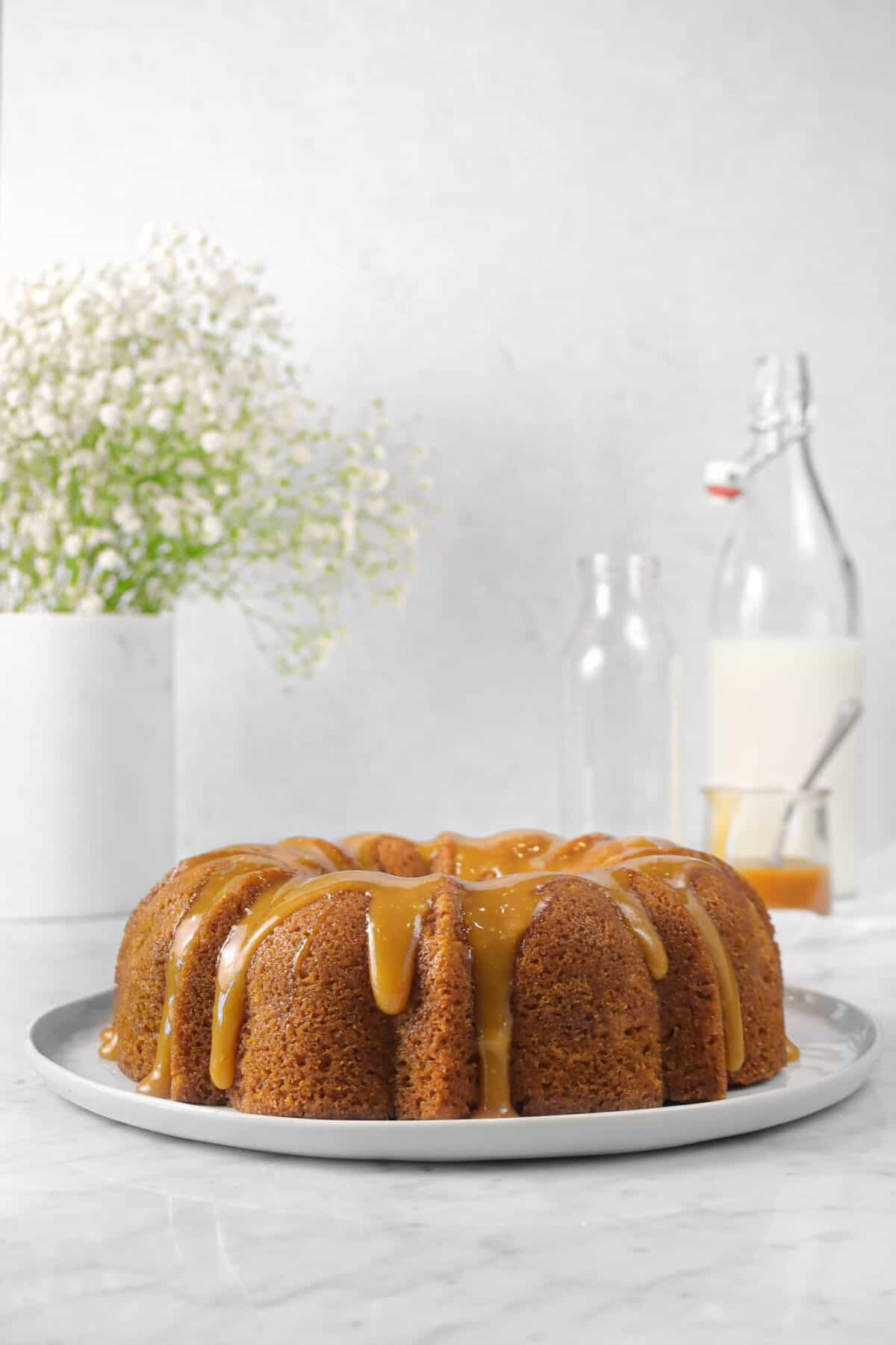 bundt cake on a white plate with caramel sauce, milk, and flowers