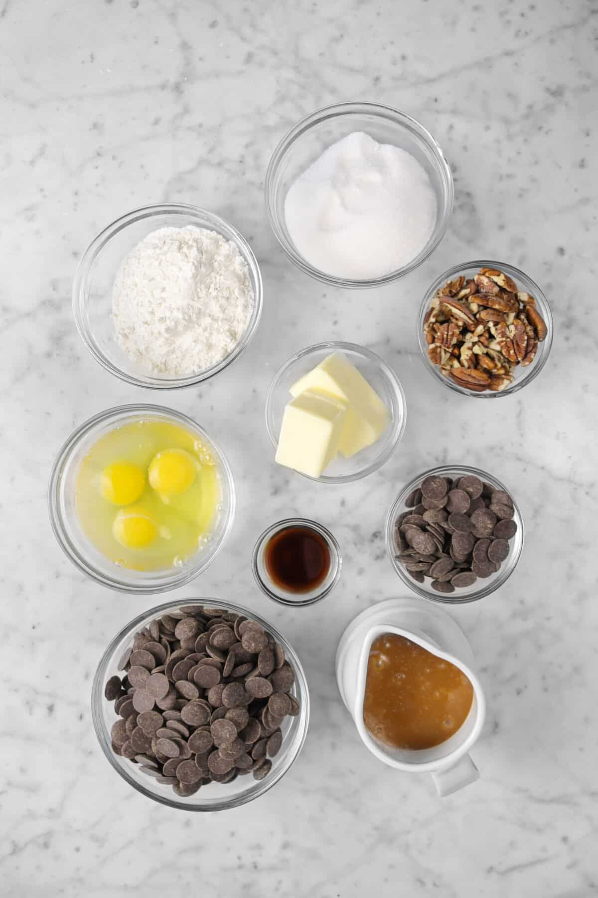 sugar, flour, pecans, butter, chocolate chips, eggs, vanilla, and caramel sauce on marble counter