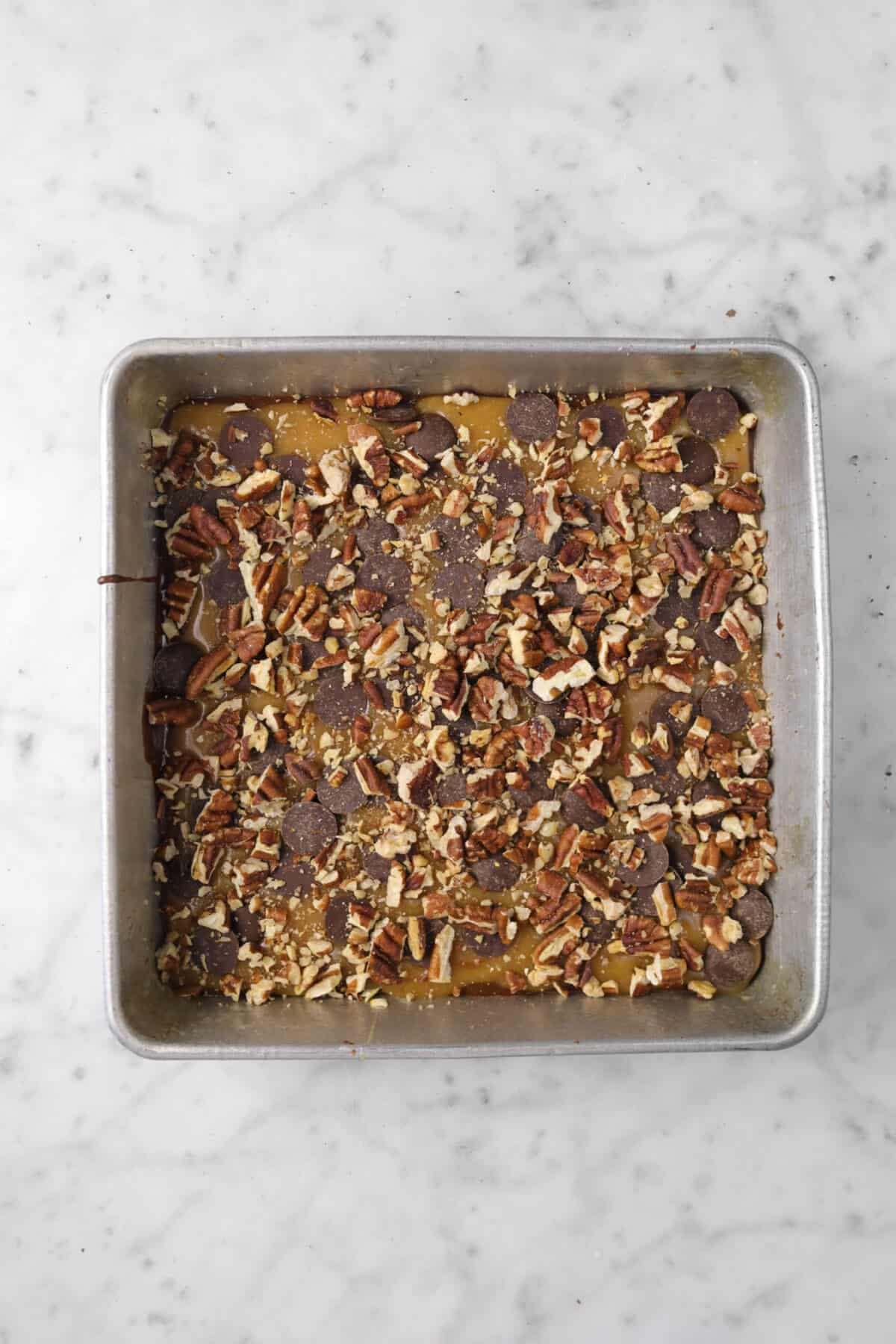 chopped toasted pecans added on top of caramel and chocolate chips