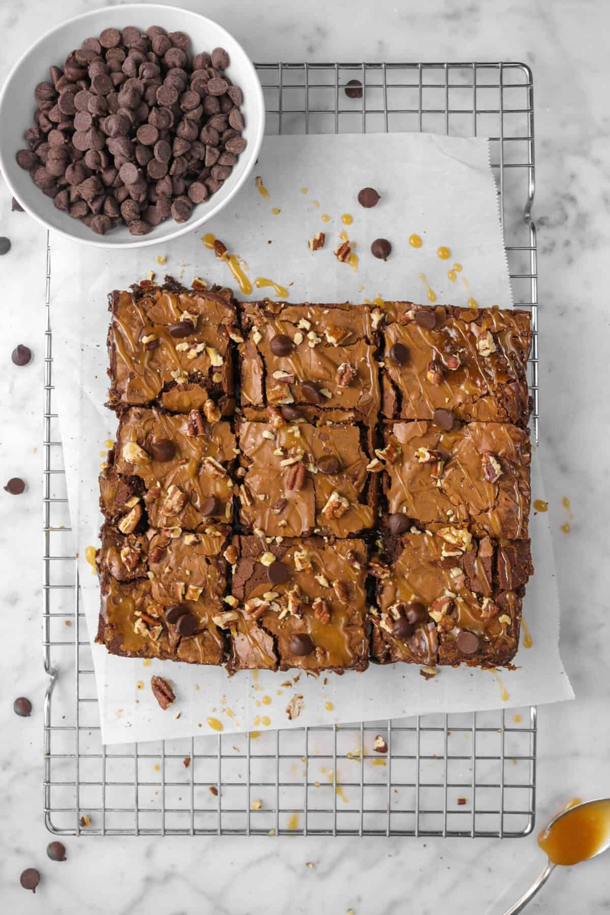 nine brownies cut on a wire rack with chocolate chips, caramel, and pecans