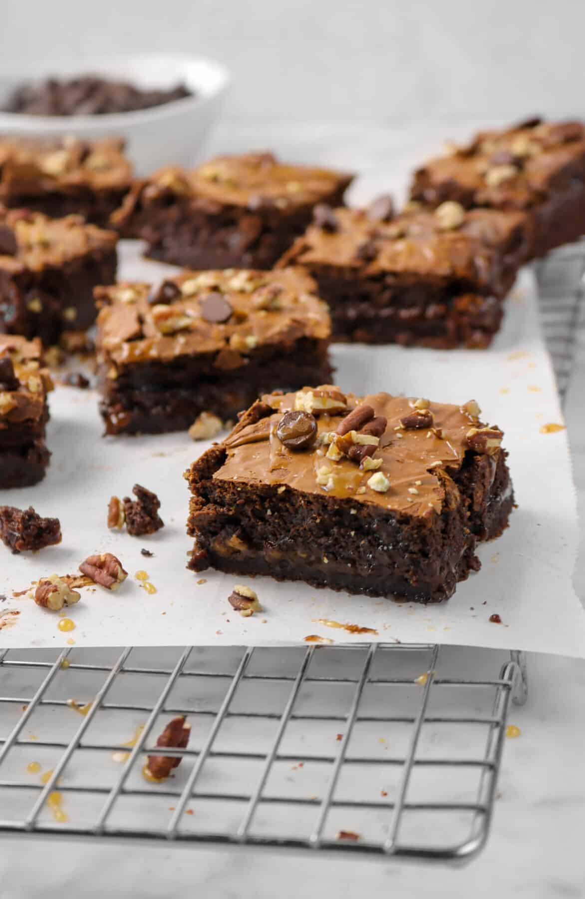 eight brownies on parchment with caramel, pecans, and chocolate chips