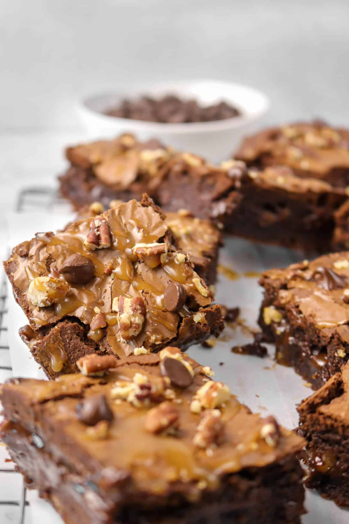 turtle brownies laying against each other on a wire cooling rack with a bowl of chocolate chips behind