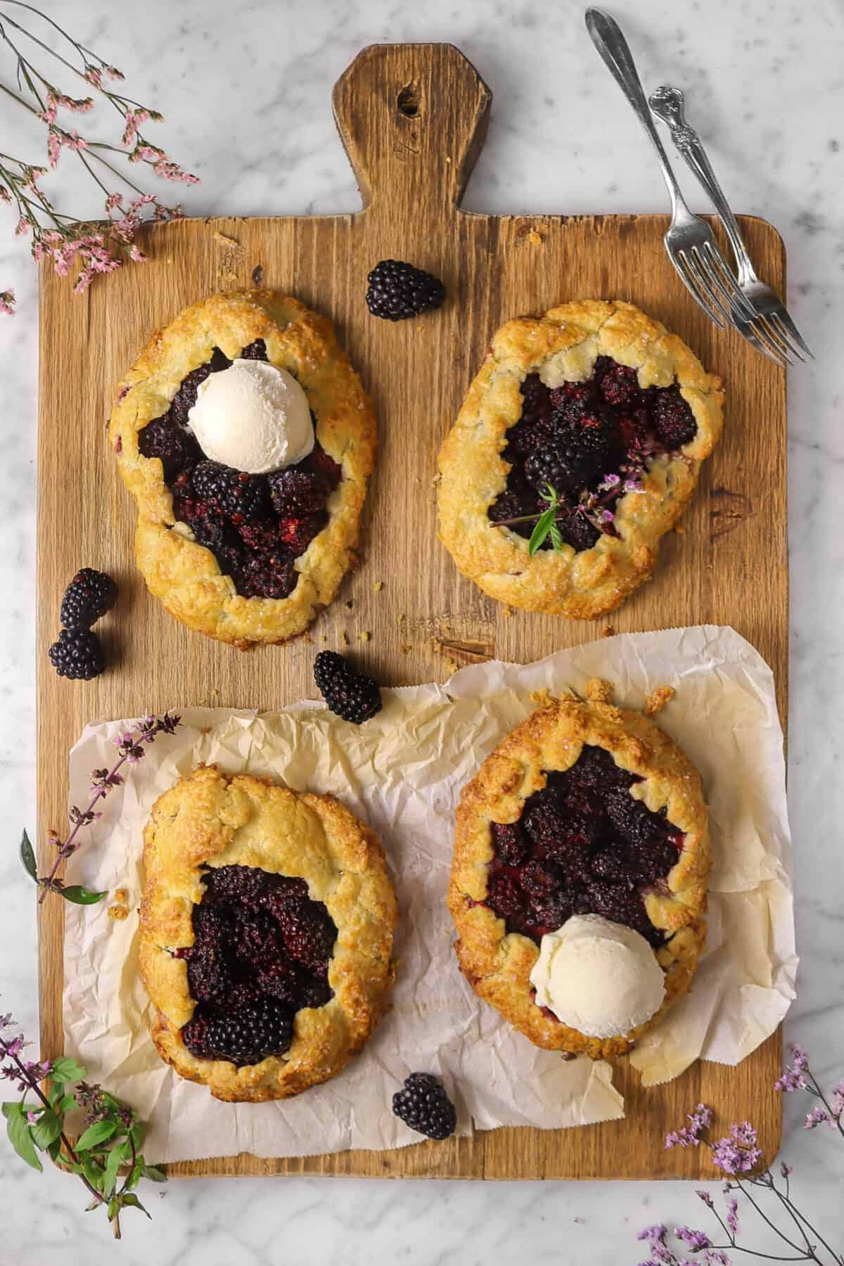 four galettes on a wood serving board with flowers, forks, and blackberries, two galettes have scoops of ice cream
