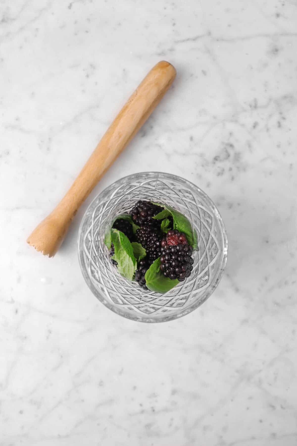 blackberries and mint in a glass with a wood muddler