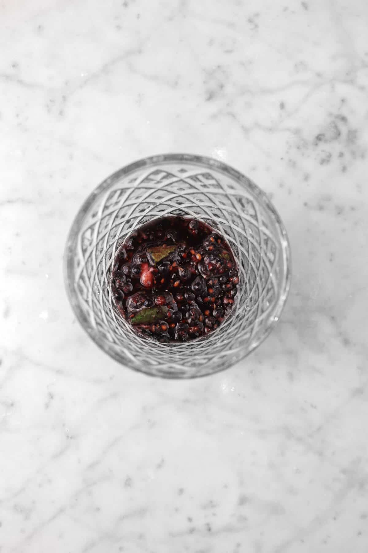 crushed mint and blackberries in a glass