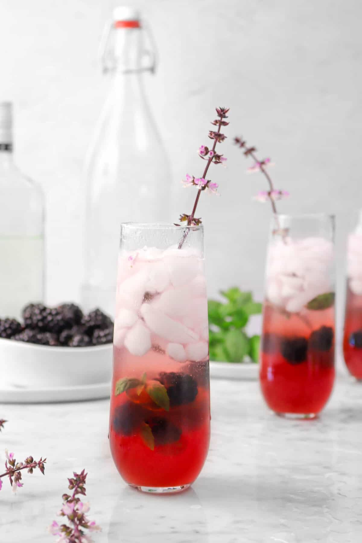 three mojitos with purple flowers, blackberries, two jars, and mint
