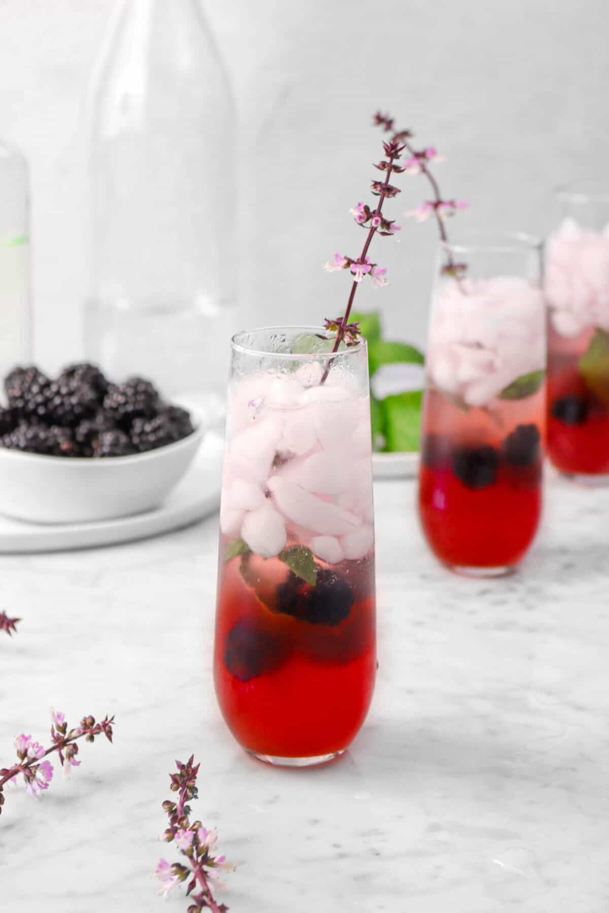 three blackberry mojitos on a marble counter with flowers, blackberries, and mint leaves