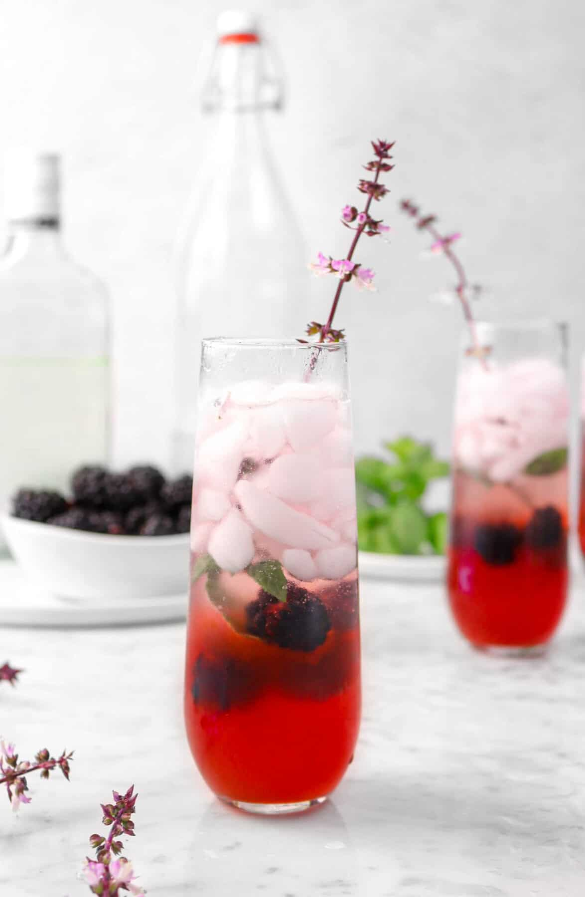 two glasses of blackberry mojito with flowers, blackberries, and mint