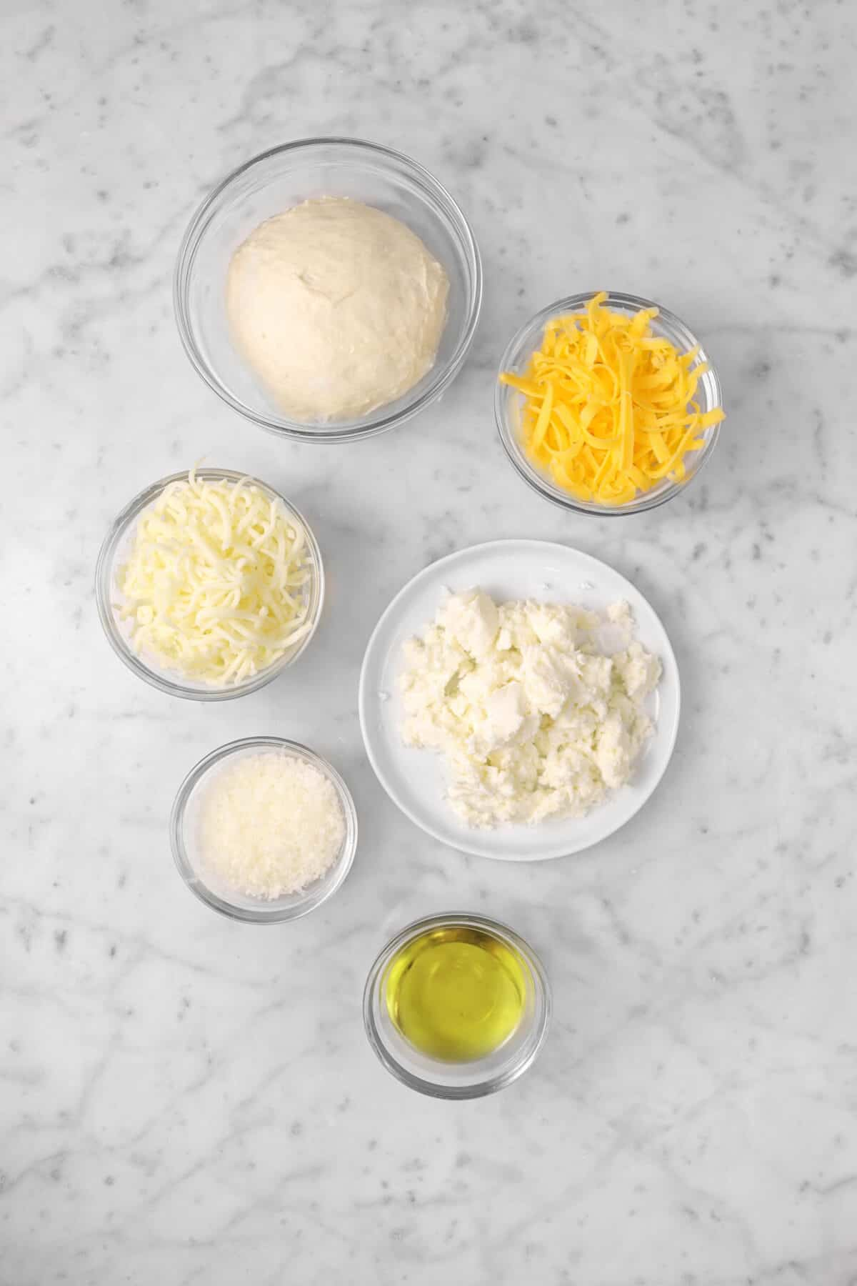 pizza dough, cheddar, mozzarella, parmesan, olive oil, fresh mozzarella on a marble counter