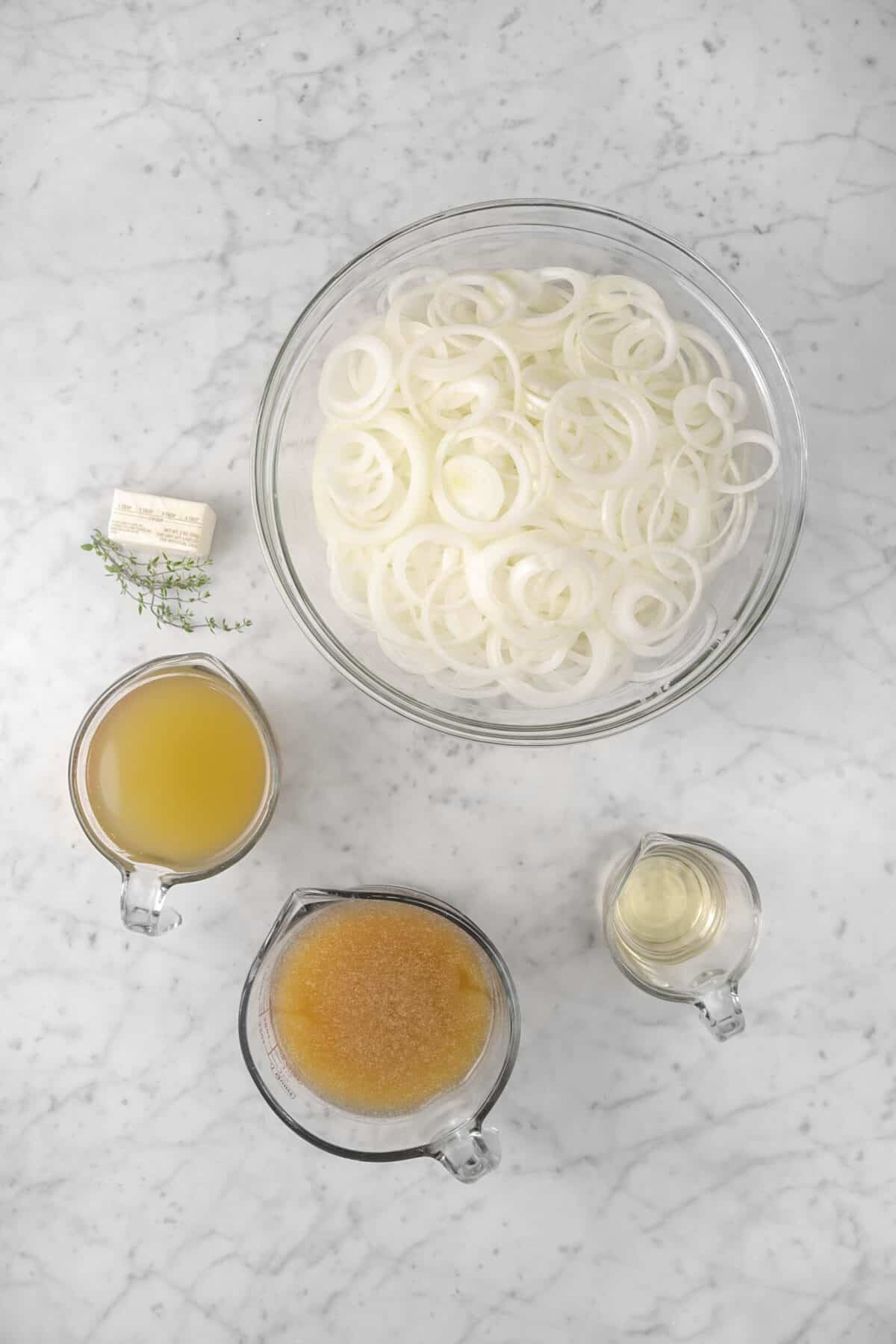 sliced onions, butter, thyme, chicken stock, beef broth, white wine on marble counter