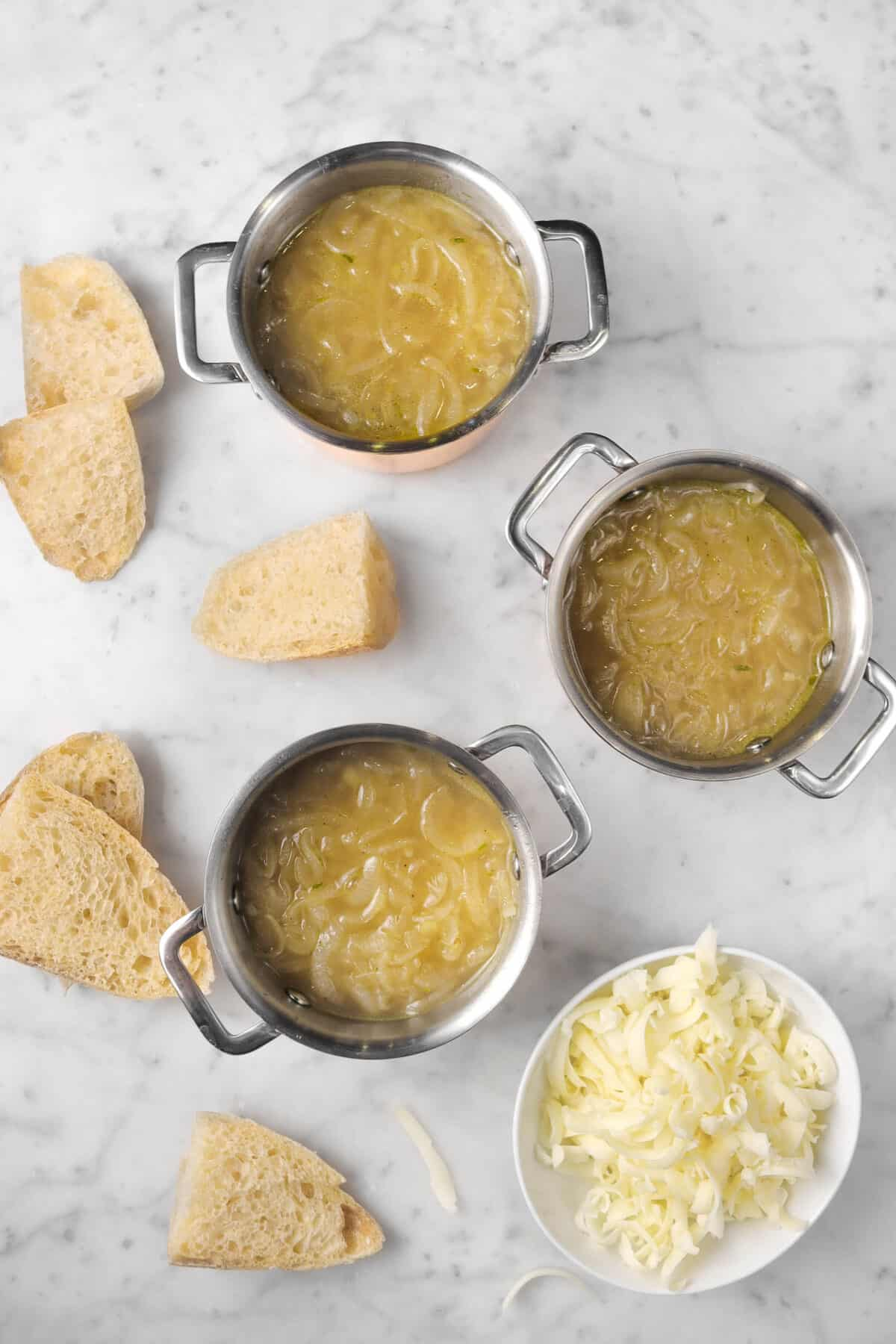 three pots of french onion soup with bread slices and a bowl of cheese