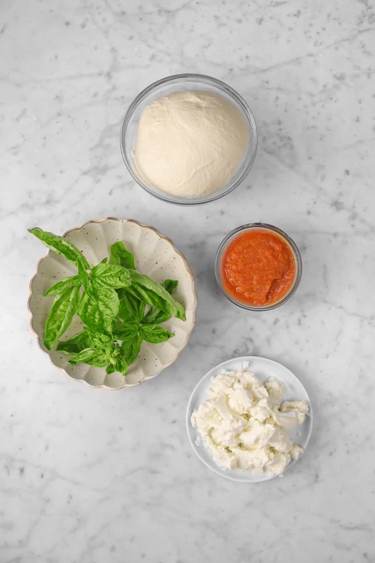 pizza dough, tomato sauce, cheese, and basil on a marble counter
