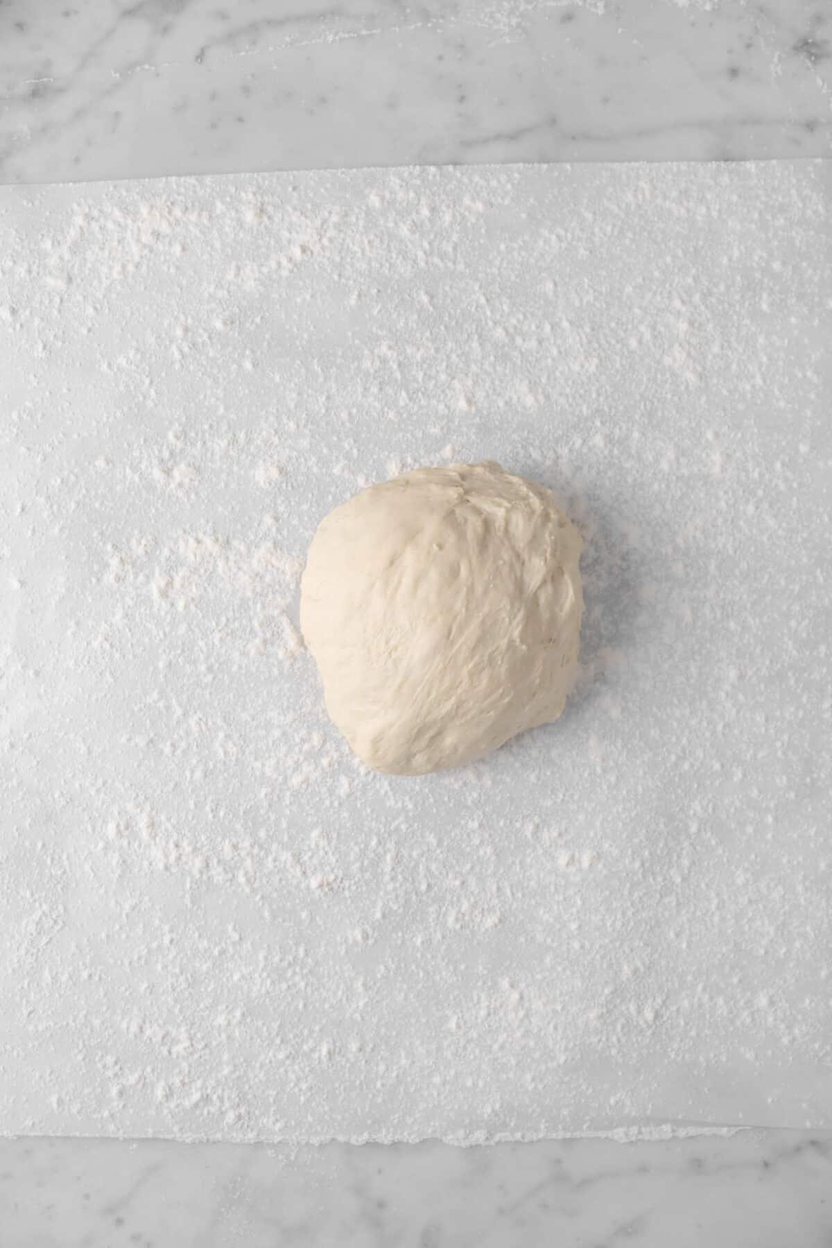 pizza dough on a piece of parchment