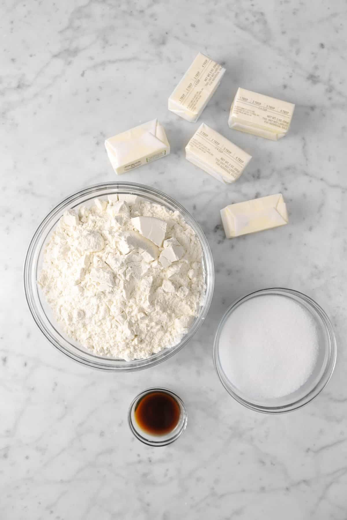 flour, butter, sugar, and vanilla on a marble counter