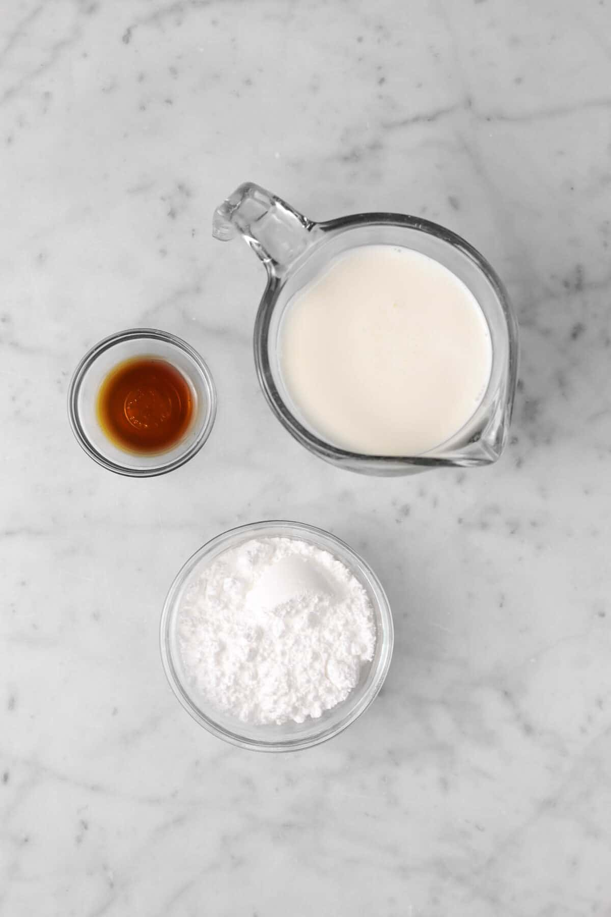 heavy cream, vanilla, and powdered sugar on marble counter