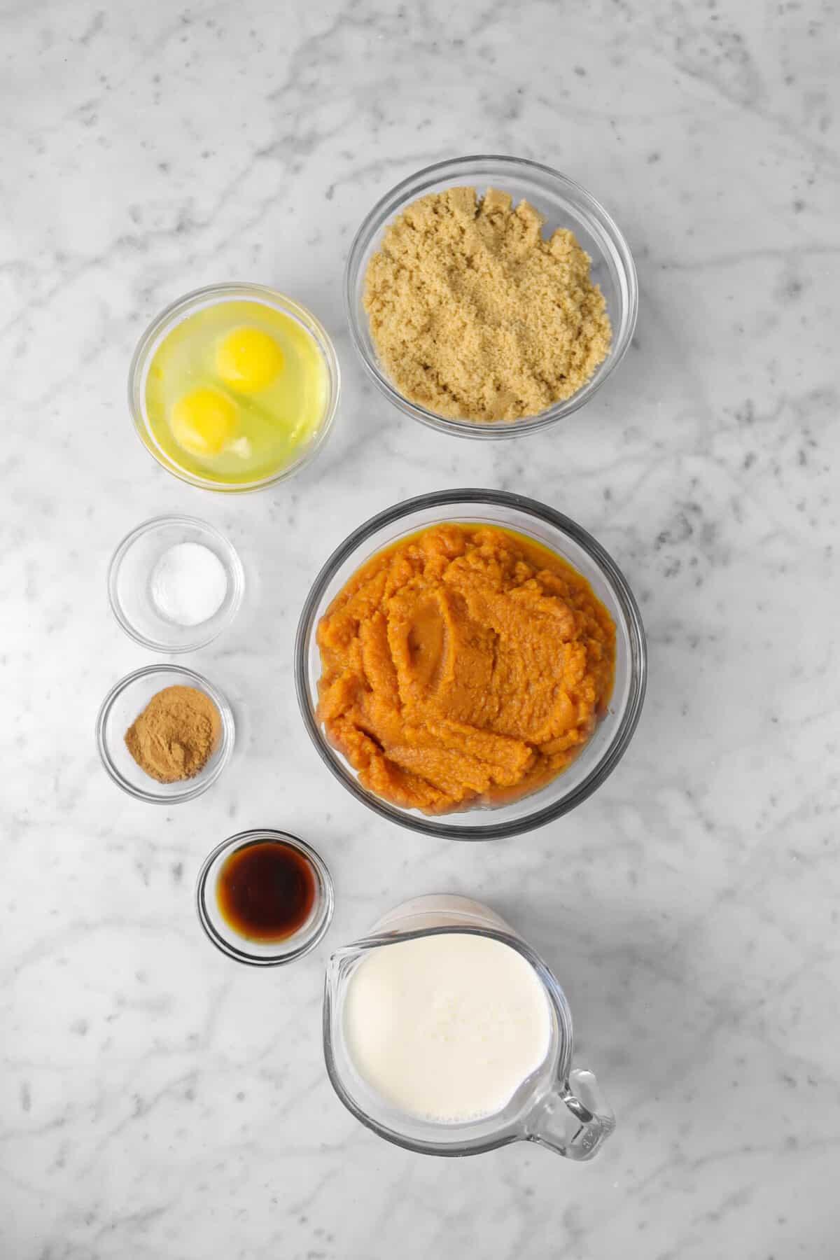 brown sugar, eggs, saly, spice, vanilla, heavy cream, and pumpkin puree on a marble counter