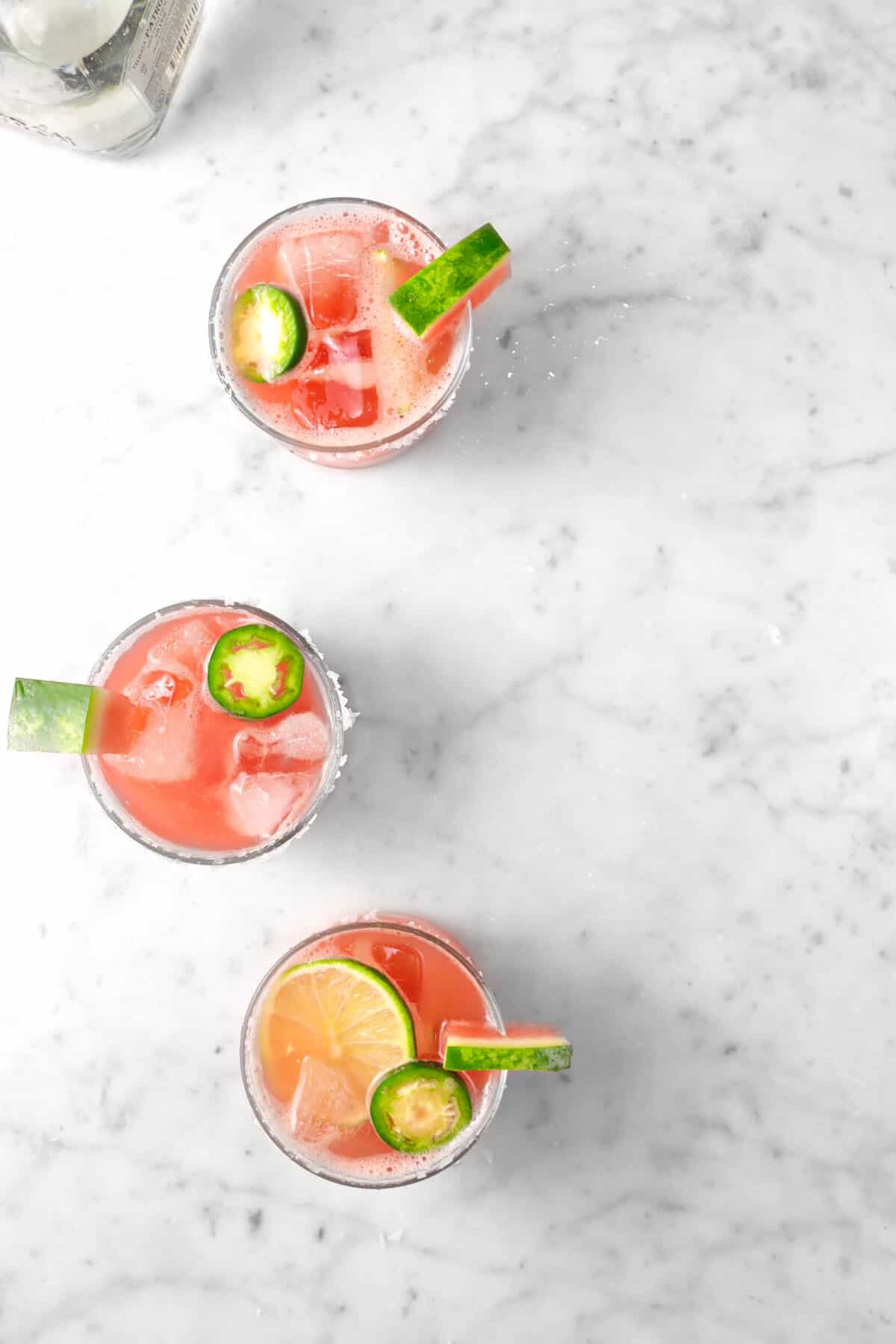 three glasses of watermelon margarita on marble counter