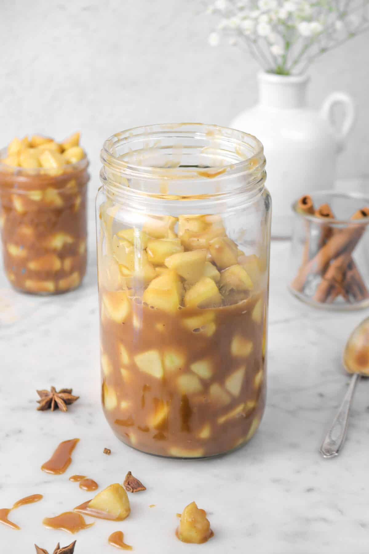 pie filling in a jar on a marble counter with cinnamon sticks and flowers