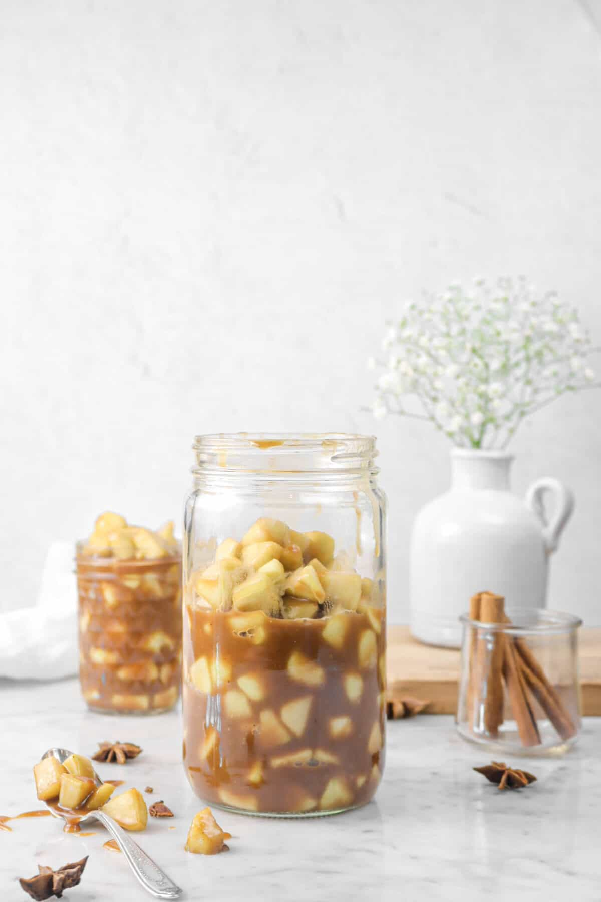 pie filling in a glass jar with spices, a spoon, and white flowers
