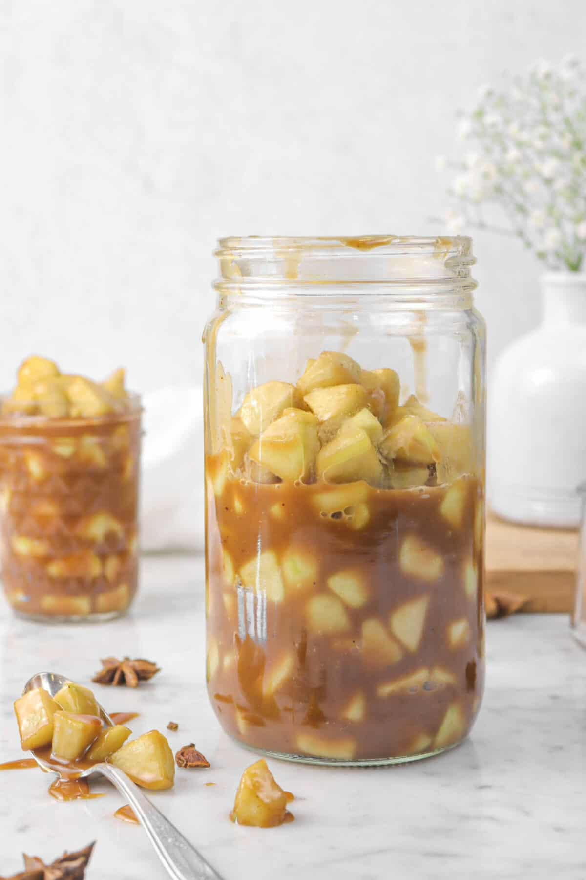 a jar of apple pie filling with another jar behind and a spoon