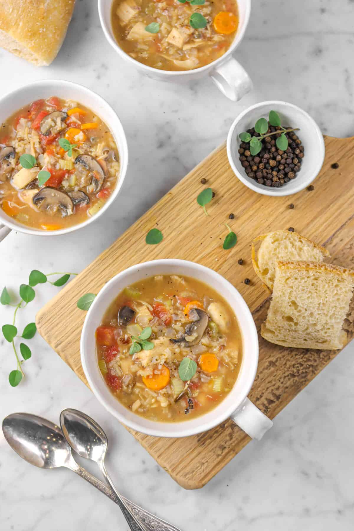 three mugs of chicken and wild rice soup, one on a serving board with bread and spoons
