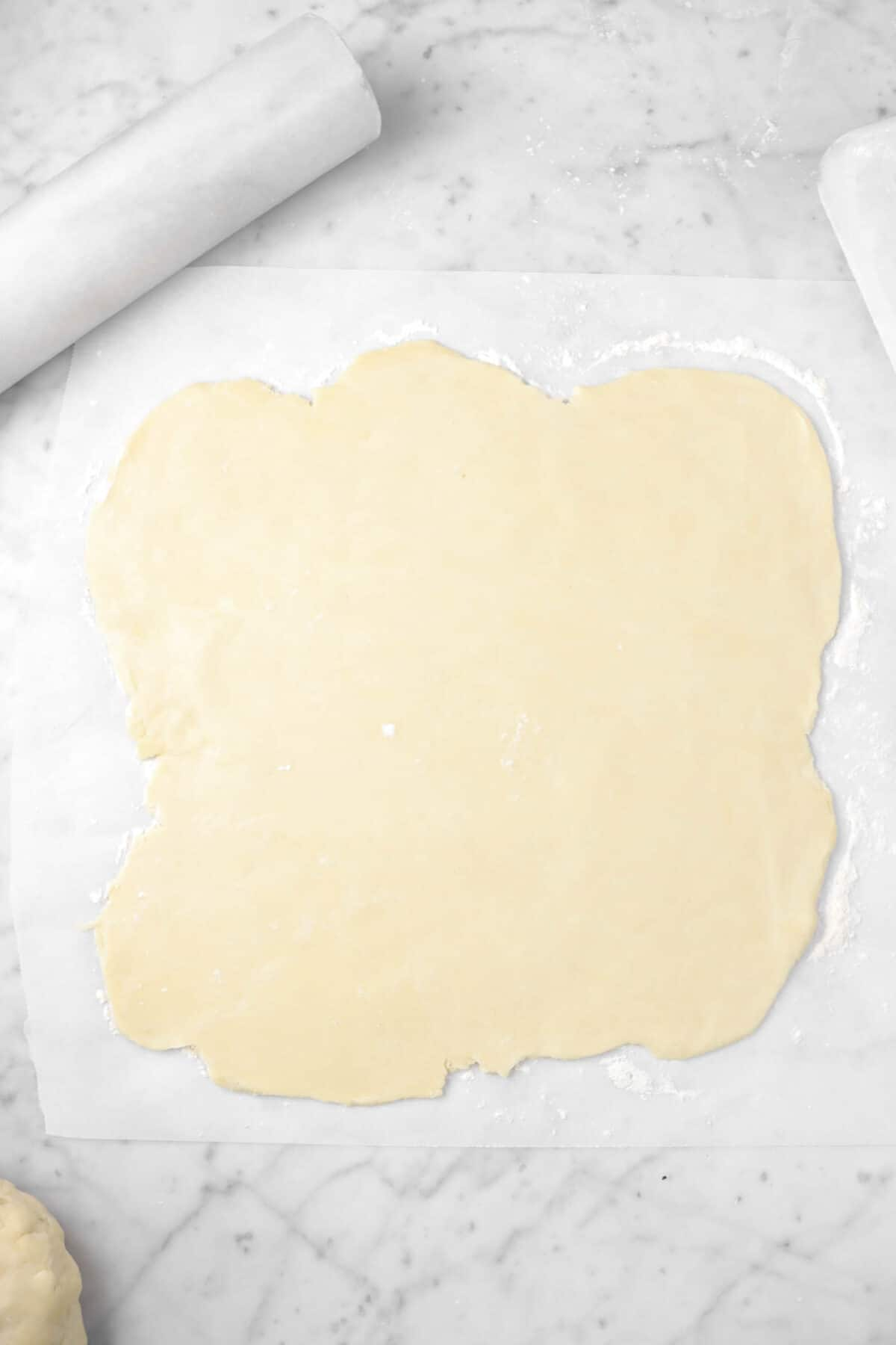 pie dough rolled out on parchment